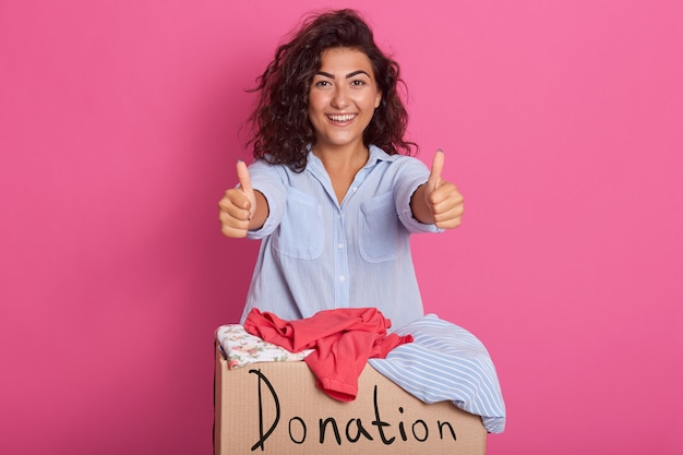 Horizontal shot of cheerful volunteer standing isolated over pink near box with inscription donation, full of donated clothes, brunette doing good things and showing ok sigh.