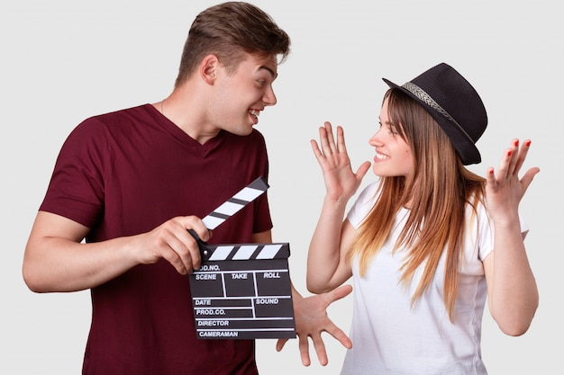 Horizontal shot of cheerful woman and man look positively at each other, gesture actively, have hesitant expressions, holds clapper board