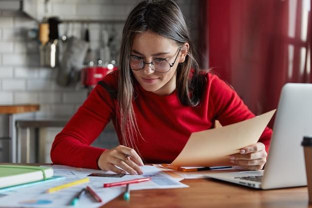 Colpo orizzontale di donna allegra si siede al tavolo della cucina recensioni finanze, si siede davanti al computer portatile aperto