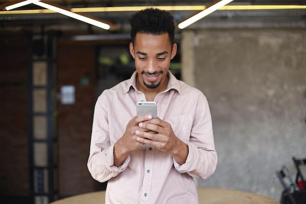 Colpo orizzontale di allegro giovane ragazzo barbuto con pelle scura digitando un messaggio al suo amico sul cellulare e sorridendo con gioia, indossando abiti casual mentre posa sopra l'interno del caffè della città