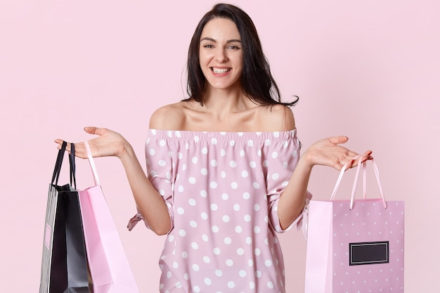 Horizontal shot of cheerful young european woman with black long hair, holds shopping bags in both hands, dressed in pink polka dot dress