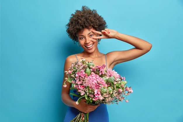 Horizontal shot of cheerful young woman shows peace gesture holds big bouquet of flowers smiles broadly has festive mood isolated over blue wall