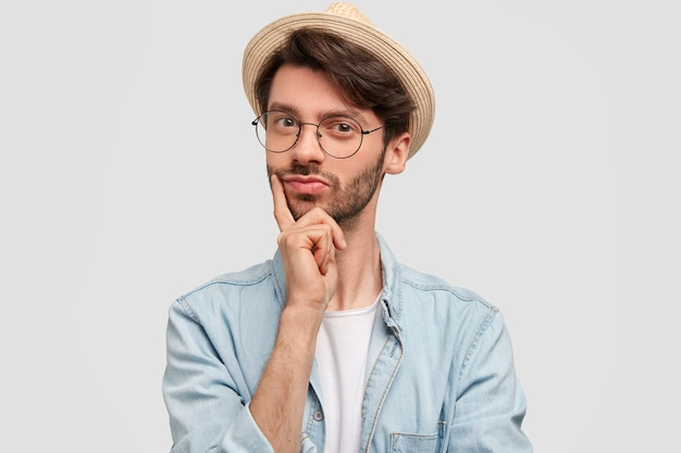 Horizontal shot of confident bearded male keeps finger on chin