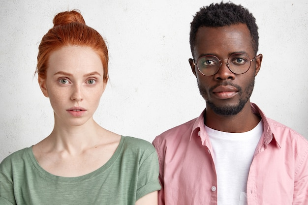 Horizontal shot of confident interracial female and male students meet after classes to prepare project work