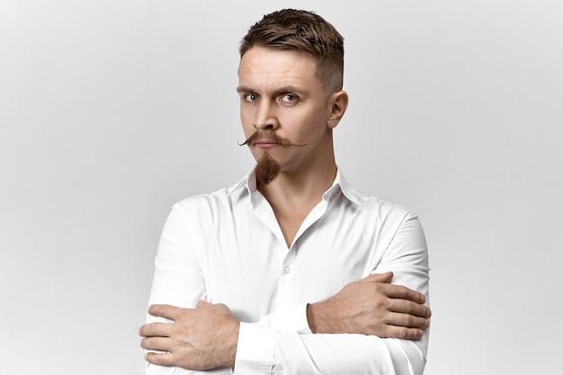 Horizontal shot of confident successful young manager in white shirt working at office, posing with arms crossed against blank gray wall background with copyspace for your text or promotional content