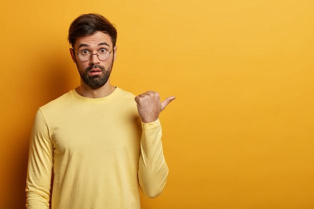 Inquadratura orizzontale di un uomo barbuto confuso punta il pollice a destra, discute dell'offerta di sconto, racconta un'incredibile vendita incredibile, indossa occhiali e maglione, copia spazio per i tuoi contenuti promozionali
