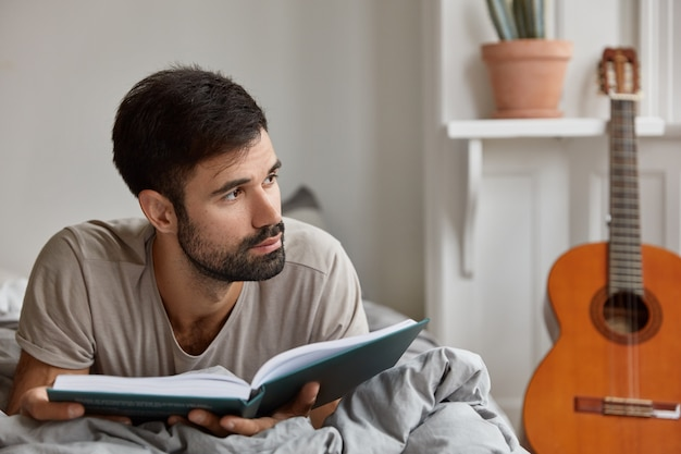 Horizontal shot of contemplative caucasian guy with dark bristle, wears casual clothes, lies on bed with book, feels lonely at home, enjoys weekend, has calm life. domestic atmosphere, reading concept
