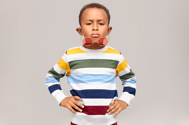 Horizontal shot of cool handsome afro american child having confident facial expression keeping hands on his waist, stylish round pink shades falling down his nose. childhood and fashion concept