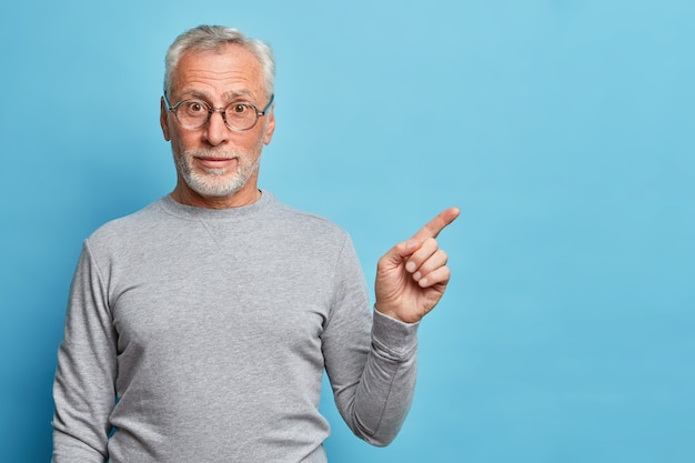 Horizontal shot of curious grey haired senior man points index finger away in blank space shows place for your advertisement wears casual jumper isolated over blue wall