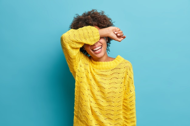 Horizontal shot of curly haired positive woman laughs sincerely and covers eyes with arm laughs at funny joke dressed in yellow knitted jumper isolated on blue wall