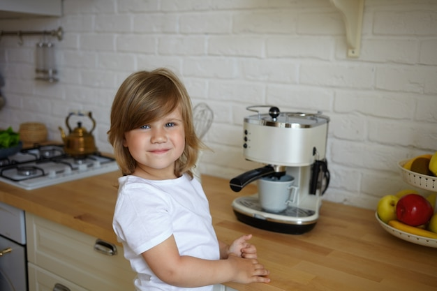 Horizontal shot of cute carefree female kid of preschool age wearing white t-shirt having happy look, standing at kitchen table, making coffee for her father. carefree childhood and cooking concept