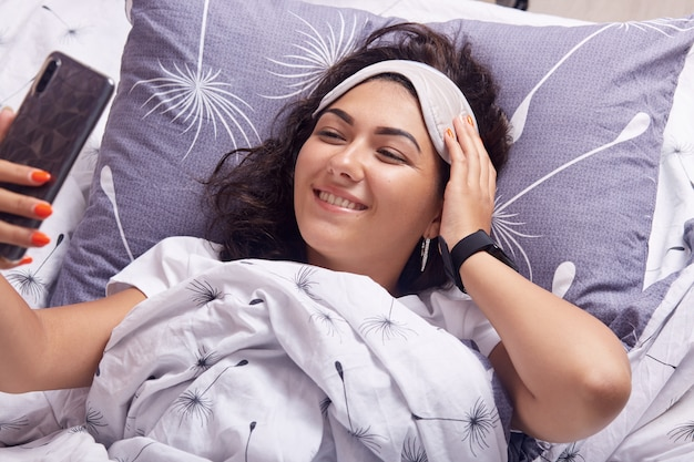 Horizontal shot of cute woman in bed with mobile phone making selfie, looking at device screen with charming happy smile, keeps hand on forehead on sleeps mask, laying in bed under white blanket.