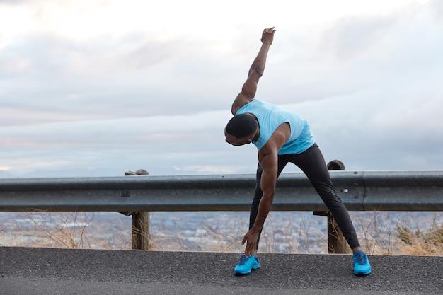 Inquadratura orizzontale dell'uomo dalla pelle scura si appoggia ai piedi, fa esercizi di stretching, ha una forma del corpo muscoloso, sta sull'asfalto sopra il cielo azzurro con lo spazio della copia per il contenuto pubblicitario, testo
