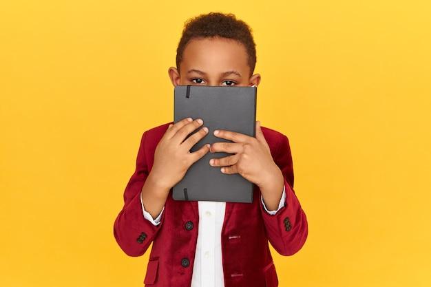 Horizontal shot of dark skinned schoolboy wearing velvet jacket holding black notebook covering face, doing homework.