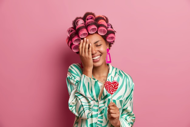 Horizontal shot of dark skinned woman stands with eyes closed, makes face palm, has fun at home, holds delicious heart shaped lollipop, wears hair rollers, smiles broadly, isolated on pink wall