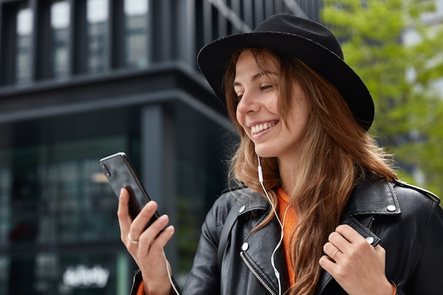 Horizontal shot of delighted female model in stylish black hat and leather jacket, focused in smart phone device
