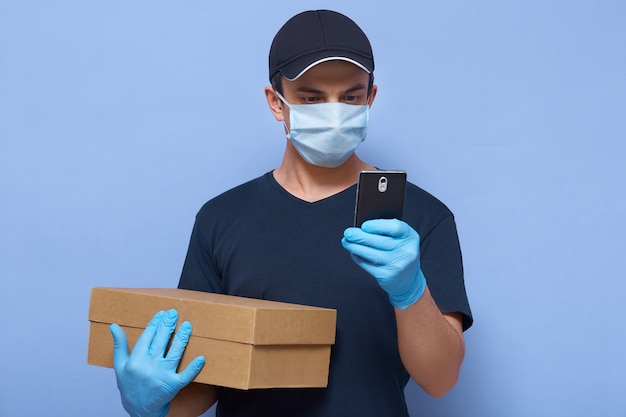 Horizontal shot of delivery man with his smart phone in hands, finding write delivery address or call client, wearing protective clothing to prevent spreading corona virus .