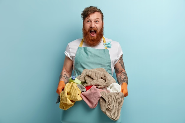 Horizontal shot of desperate redhead man shouts with annoyance, holds basin with pile of dirty laundry