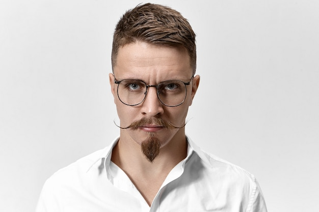 Inquadratura orizzontale di uomo d'affari infastidito dispiaciuto in bicchieri e camicia bianca formale che propone alla parete in bianco dello studio