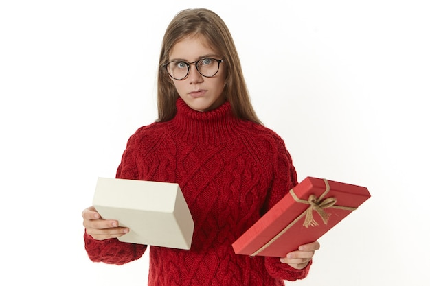 Horizontal shot of displeased or confused young woman wearing spectacles and knitted sweater posing holding open box, being puzzled while receiving wrong present that she does not like