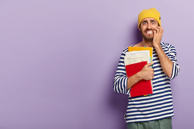 Horizontal shot of displeased man bites finger nails nervously, holds papers with notepad, wears yellow hat and striped jumper, poses on violet background blank space on left side
