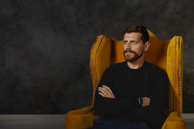 Horizontal shot of displeased offended attractive bearded man being stubborn, expressing his disrespect, sitting isolated in luxurious armchair with arms folded, looking away as if ignoring you