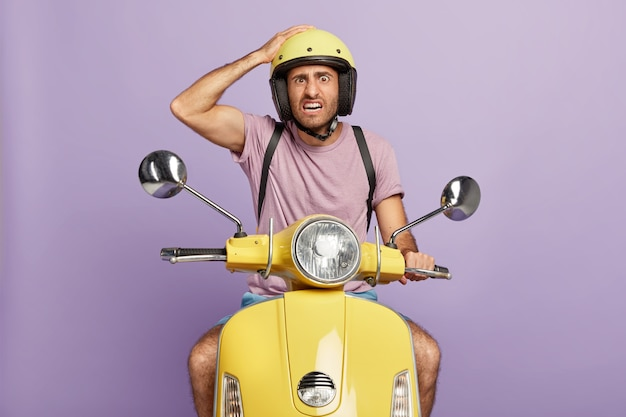 Horizontal shot of displeased unshaven male driver holds hand on helmet, poses on fast motorbike, drives quickly and transports something, wears casual purple t shirt. people and transport concept