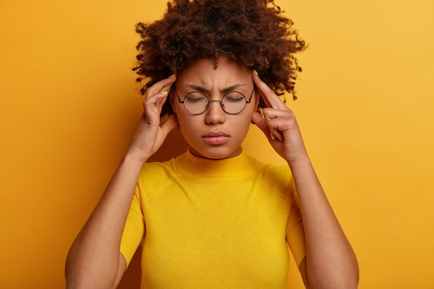 Horizontal shot of dissatisfied dark skinned model feels headache, suffers from pain in temples, closes eyes, needs painkillers, wears round spectacles and casual clothes, poses against yellow wall
