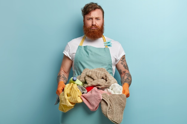 Horizontal shot of dissatisfied foxy man with beard, wears t shirt and apron, holds stuck of dirty clothes, frowns face, isolated over blue wall, uses chemical detergent. housekeeping concept