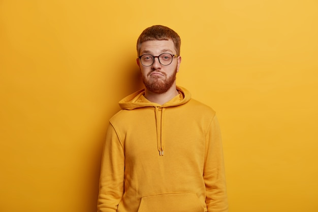 Horizontal shot of doubtful bearded man with ginger hair and beard purses lips and looks confusingly , hears puzzled news, has specific appearance, wears yellow hoodie and spectacles