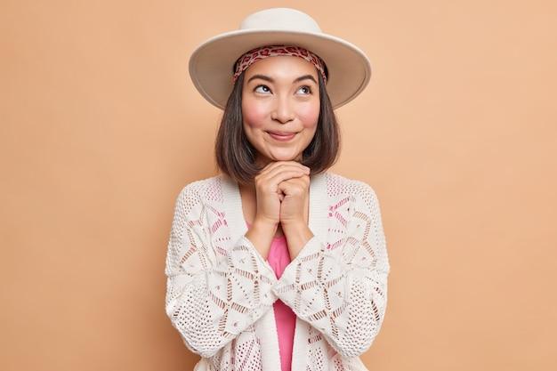 Il colpo orizzontale della donna asiatica sognante tiene le mani sotto il mento pensa a qualcosa di piacevole indossa il maglione lavorato a maglia bianco fedora fa piani in mente isolati sul muro beige