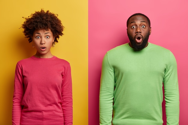 Horizontal shot of embarrassed shocked ethnic couple stare with bugged eyes , fascinated by something terrible, gasps from wonder, wear pink and green jumpers, pose over colorful  wall