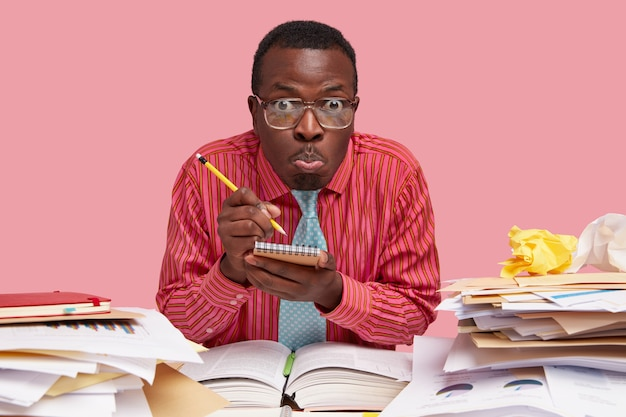 Horizontal shot of emotive black man writes down in notebook information, sits at desktop alone, makes grimace, wears pink shirt and tie, works on report
