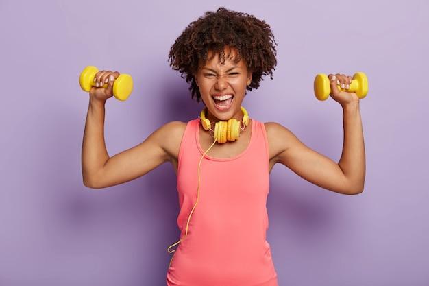 Colpo orizzontale di eccitata donna afro felice alza le braccia con manubri, gode di allenamento sportivo con musica in cuffia, vestita con gilet rosa casual, pose al coperto. persone