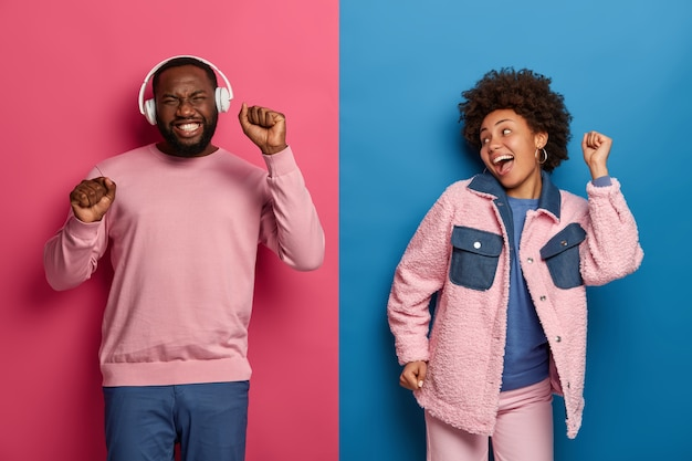Horizontal shot of ethnic boyfriend and girlfriend dance carefree, enjoy awesome headphones bits, smile happily, raise hands, have fun together at disco party, pose against two colored wall