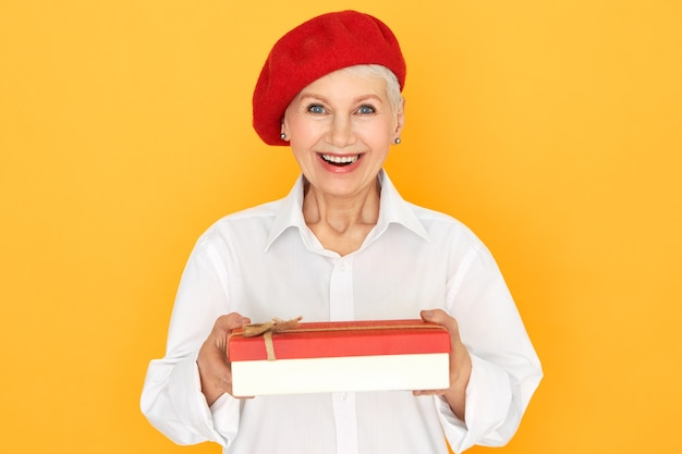 Horizontal shot of excited stylish french female pesnioner in red beret holding box, reaching out hands at camera, making gift to you. charming mature woman giving present on birthday posing isolated