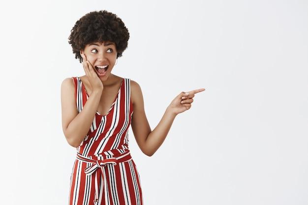 Inquadratura orizzontale di donna loquace attraente eccitata e sorpresa con i capelli ricci e la pelle scura in tuta alla moda che punta e guarda impressa nella giusta direzione, stupita