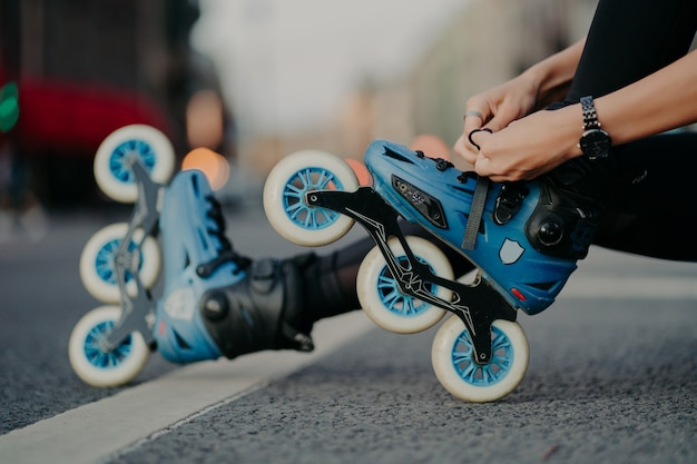Horizontal shot of faceless woman puts on rollerskates rides on road poses against urban background involdved in active sport. people hobby recreation extreme sport active lifestyle concept.