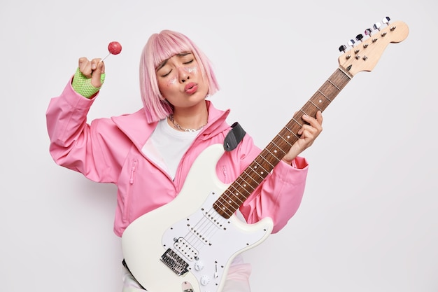 Horizontal shot of fashionable female guitarist sings song along poses with electric acoustic guitar holds lollipop plays rock music