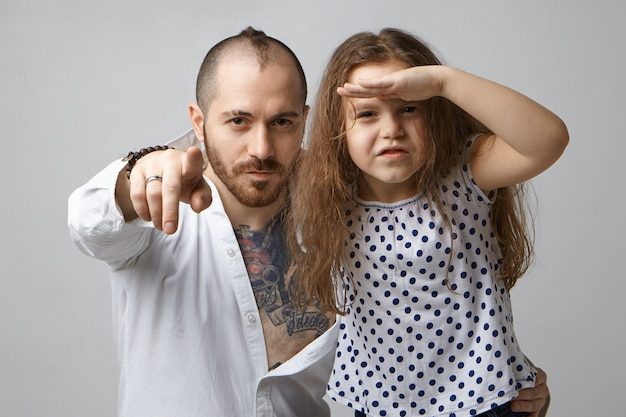 Horizontal shot of fashionable young father with beard and tattoo on chest pointing finger at camera