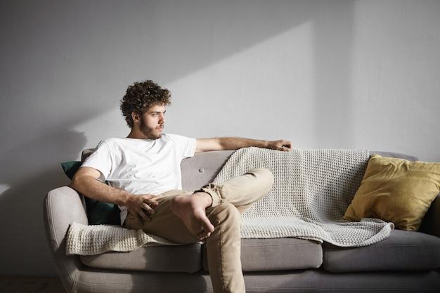 Inquadratura orizzontale di giovane scapolo caucasico di trent'anni alla moda con capelli ondulati e barba folta comodamente seduto sul divano nel soggiorno, con sguardo serio, cercando di rilassarsi dopo il lavoro