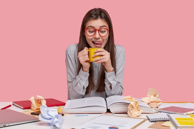 Horizontal shot of female student holds mug of aromatic drink, licks lips, wears spectacles and shirt, reads book, prepares for exam