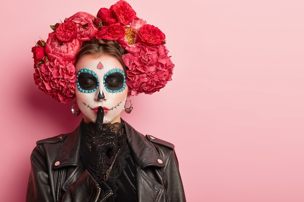 Horizontal shot of female with creative makeup, dressed in black outfit, shows silence hand gesture, keeps eyes shut, poses against pink wall.