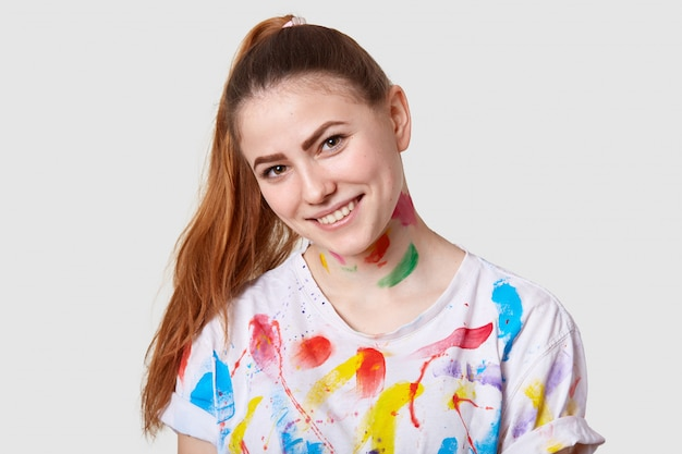 Horizontal shot of female with pony tail, tilts head, has creative occupation, dressed in casual t shirt with watercolour stains, poses on white. people and inspiration