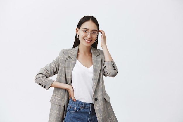 Horizontal shot of feminine fashionable cute woman in glasses and trendy jacket, holding hand on waist, standing in model pose and touching hair strand gently, smiling broadly