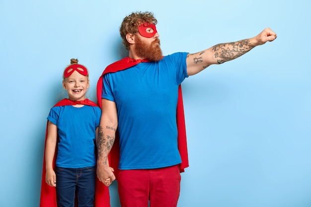 Horizontal shot of feraless strong ginger father holds hand on small kid