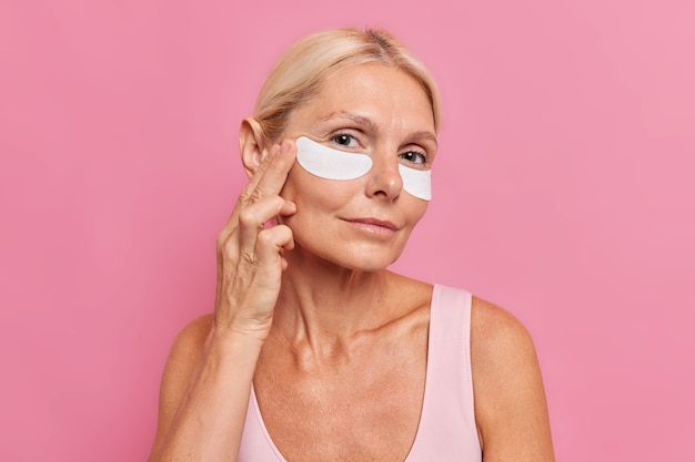 Horizontal shot of forty years old blonde woman applies beauty patches under eyes undergoes anti aging procedures looks attentively at camera isolated over pink wall