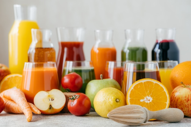 Horizontal shot of fresh fruit and vegetables on white table, glass jars of juice and orange squeezer.