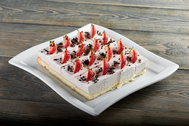 Horizontal shot of freshly baked delicious cheesecake decorated with strawberries on top wooden table pastry cooking baking dessert breakfast sweet concept.