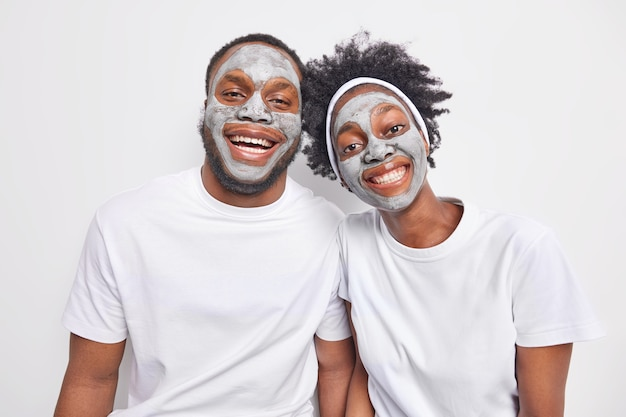 Horizontal shot of friendly ethnic woman and man stand closely to each oother smile broadly show white teeth take care of complexion wear nourishing beauty mask for healthy skin have good relations